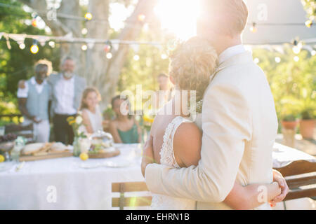 Young couple embracing in garden during wedding reception - Stock Photo