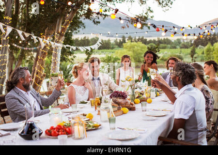 Young couple and their guests sitting at table during wedding reception in garden - Stock Photo