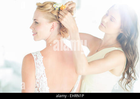 Bridesmaid helping bride with hairstyle in garden - Stock Photo