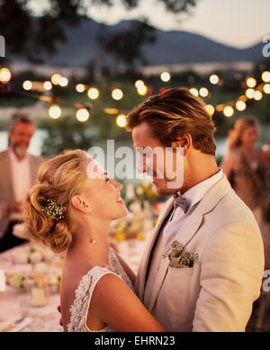 Portrait of young couple dancing in garden during wedding reception - Stock Photo