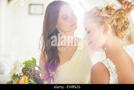 Bridesmaid helping bride with hairstyle in bedroom - Stock Photo