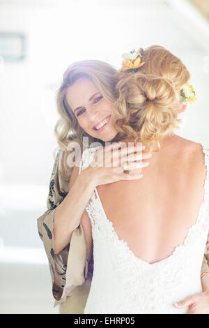 Portrait of smiling matron of honor embracing bride - Stock Photo
