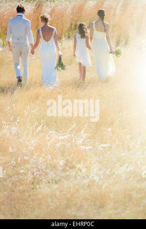 Young couple with bridesmaid and girl walking in meadow - Stock Photo