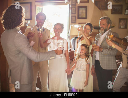 Young couple and guests toasting with champagne at wedding reception - Stock Photo