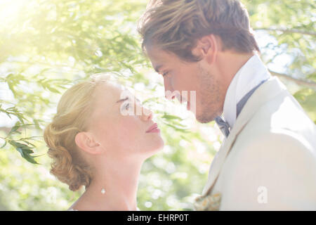 Young couple facing each other in domestic garden - Stock Photo