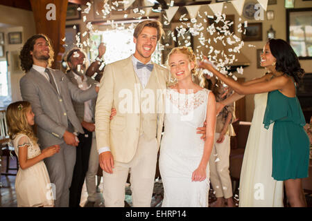 Portrait of smiling young couple standing in falling confetti during wedding reception - Stock Photo