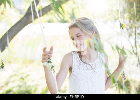 Smiling bridesmaid playing with decorations in domestic garden during wedding reception - Stock Photo