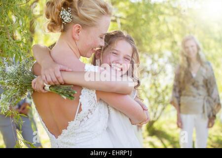Bride embracing bridesmaid at wedding reception in domestic garden - Stock Photo
