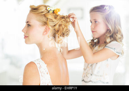 Bridesmaid helping bride with hairstyle in domestic room - Stock Photo