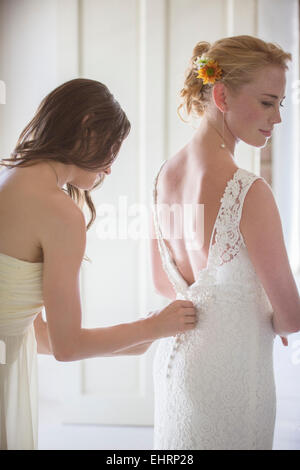 Bridesmaid helping bride with dressing in domestic room - Stock Photo