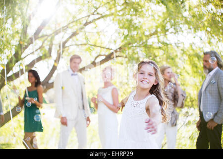 Bridesmaid playing with bubbles at wedding reception in domestic garden - Stock Photo