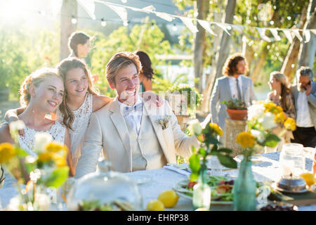 Young couple and bridesmaid during wedding reception in domestic garden - Stock Photo
