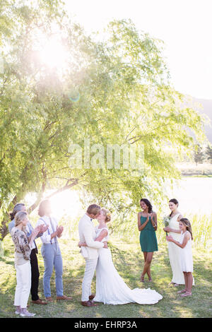 Young couple embracing and kissing during wedding ceremony in domestic garden - Stock Photo