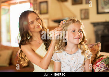 Bridesmaid helping girl with hairstyle in domestic room - Stock Photo