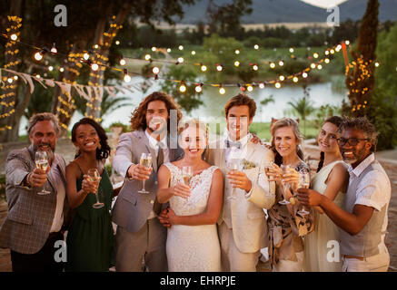 Portrait of young couple with guests toasting with champagne during wedding reception at dusk - Stock Photo