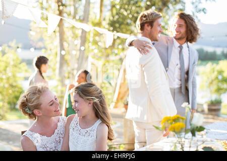 Bride talking to bridesmaid during wedding reception in domestic garden - Stock Photo