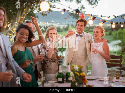 Young couple and guests toasting with champagne during wedding reception in domestic garden - Stock Photo