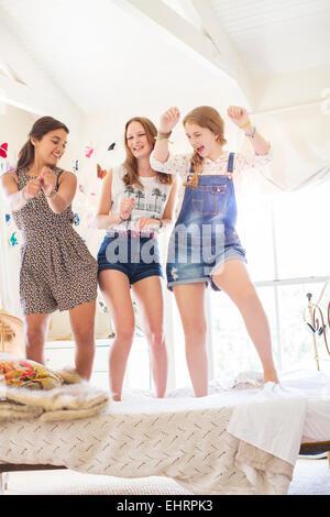 Three teenage girls dancing on bed in bedroom - Stock Photo