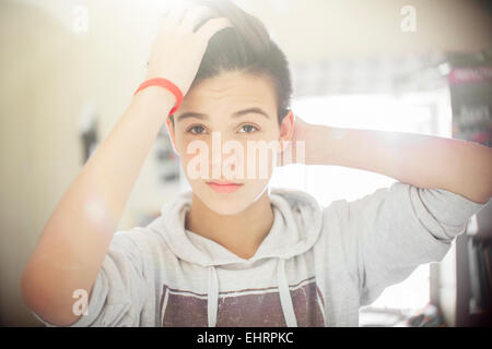 Portrait of teenage boy with hand in hair - Stock Photo