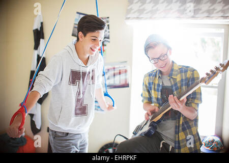 Two teenage boys having fun and playing electric guitar in room - Stock Photo