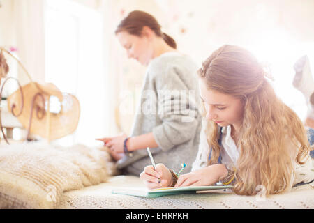 Two teenage girls on bed writting in notepads - Stock Photo