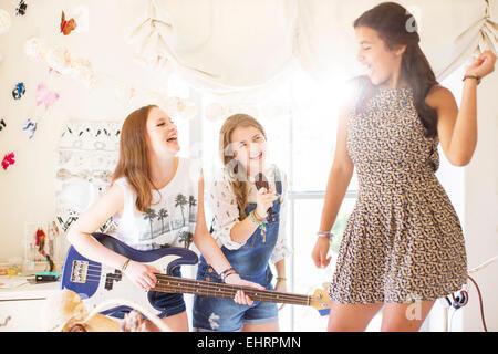 Three teenage girls playing music and singing in room - Stock Photo