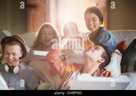 Group of teenagers eating pizza on sofa in living room - Stock Photo