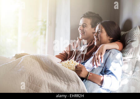 Teenage couple lying in bed and watching tv - Stock Photo