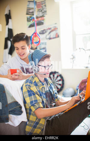 Two teenage boys using electronic devices in room - Stock Photo
