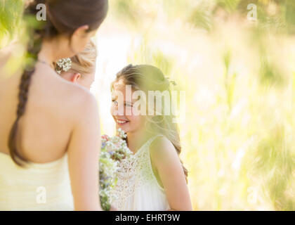Bridesmaid with bouquet of flowers during wedding reception in garden - Stock Photo