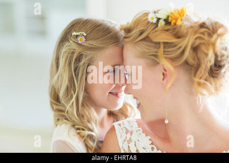 Bride and bridesmaid facing each other smiling - Stock Photo