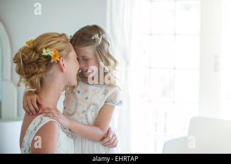 Bride and bridesmaid facing each other and smiling in bedroom - Stock Photo