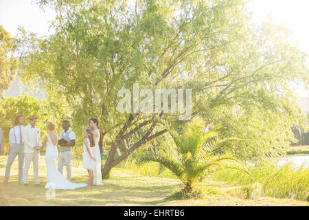 Young couple and their guests standing in garden attending wedding ceremony - Stock Photo