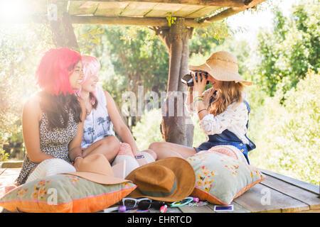 Three teenage girls taking photos in tree house in sunlight - Stock Photo