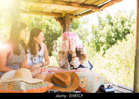 Three teenage girls playing in tree house in summer - Stock Photo