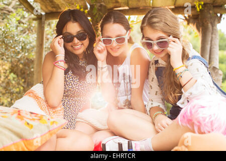 Portrait of three teenage girls wearing sunglasses and sitting in tree house - Stock Photo