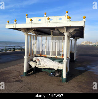 A Homeless man enjoys a cigarette while wrapped up in a sleeping bag from the cold in an Edwardian seafront shelter - Stock Photo