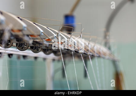 Image thread in holders on loom - Stock Photo