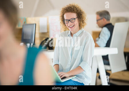 Portrait of woman using laptop and laughing, man working in background - Stock Photo