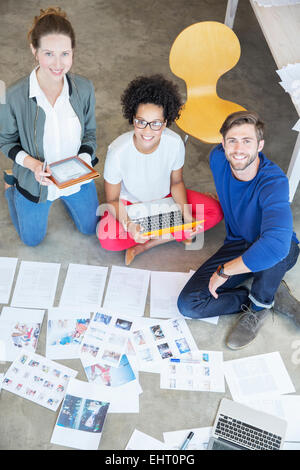 Portrait of three young people sitting on floor and working together - Stock Photo