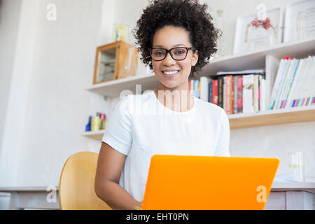 Young woman working with orange laptop in studio - Stock Photo