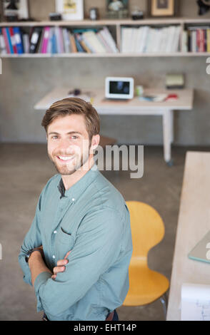 Portrait of young blonde man standing in studio - Stock Photo