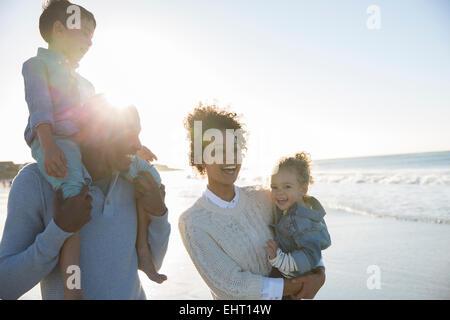 Happy family having fun on beach - Stock Photo