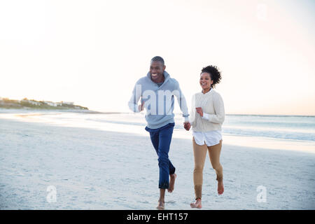 Couple holding hands and running on beach - Stock Photo