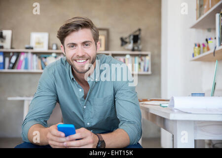 Portrait of young blonde man sitting with mobile phone - Stock Photo