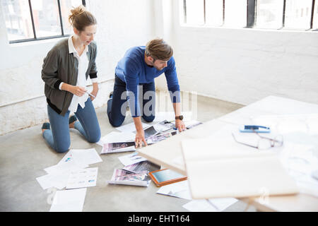 Two young people kneeling on floor and looking at documents - Stock Photo