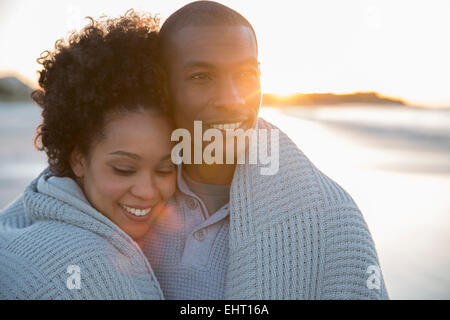 Portrait of couple wrapped in blanket on beach - Stock Photo