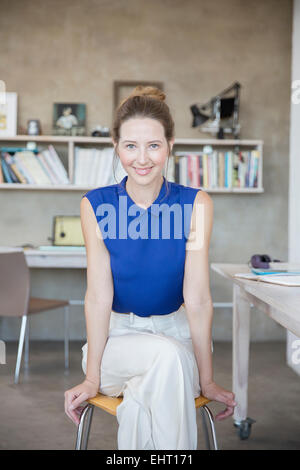 Portrait of young woman sitting on stool in studio - Stock Photo
