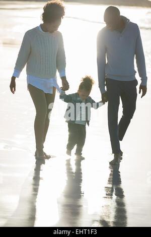 Happy family walking on beach - Stock Photo