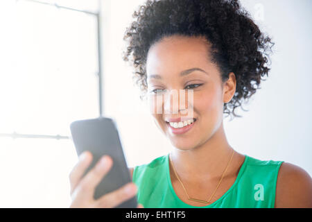 Portrait of woman with black curly hair holding mobile phone - Stock Photo